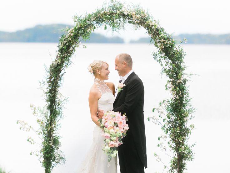 Vigseln äger rum utomhus vid vattnet, under en blomsterbåge som fint ramar in ceremonin.