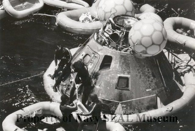 1991.0014.4 - B&W photo of Men of Underwater Demolition Teams 11 and 12 ready the Apollo command module for lifting onto elevator two of the amphibious assault ship USS New Orleans (LPH-11) following the splashdown. During the mission the Apollo linked with Soviet Soyuz spacecraft.
