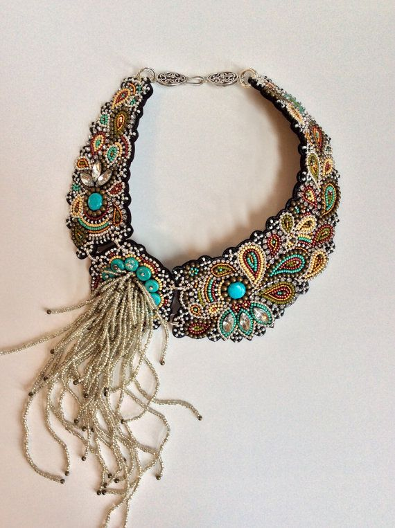 A unique, collar style bead embroidery necklace featuring three pieces of soft black leather hand embroidered with hundreds of glass seed beads in rich colors of turquoise, metallic cranberry, mustard, olive, orange, black and white. The design is accented with turquoise beads, brass and silver metal beads, rhinestones and rhinestone chain. The beadwork is covered with a thin coat of resin to keep everything in place. Features a hot mess of silver-lined rochaille fringe capped with tiny…