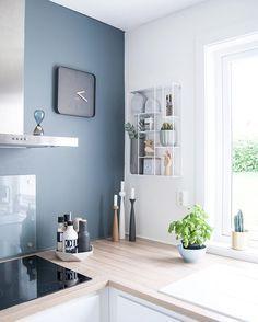Una pared en un color oscuro aporta el toque de color en una cocina típicamente nórdica en blanco y madera.