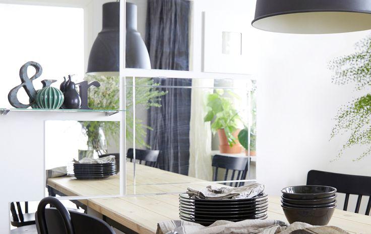 Le mur de la salle à manger est décoré de plusieurs miroirs rectangulaires et carrés placés à côté de la table.