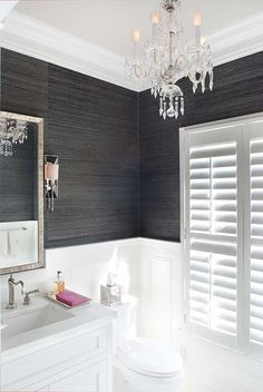 White and black bathroom features top half of walls clad in black grasscloth and bottom half of walls clad in wainscoting lined with a white washstand and a beveled mirror illuminated by a crystal chandelier.