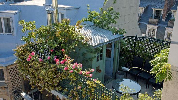 Construite sur le toit d'un immeuble parisien, au fond d'une longue terrasse étroite, cette cabane cache un mur aveugle et rappelle une maisonnette de campagne aux allures rustiques.