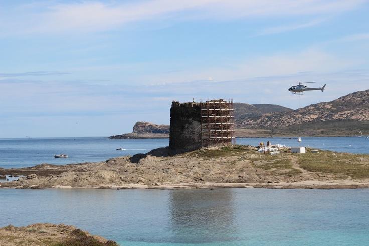 Stintino 9 maggio. Aperto il cantiere per il restauro della torre della Pelosa. Alle 10,15 l'elicottero deposita sabbia e attrezzature sull'isolotto. Read more on www.stintinonotizie.it http://tinyurl.com/cnhp2z5