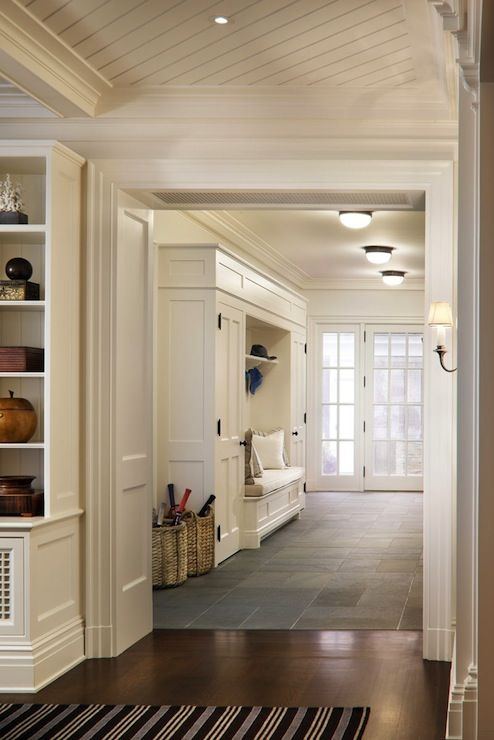 Beautiful entryway with mudroom built-ins surrounding a bench with white seat ...