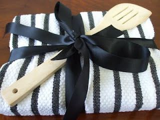 A cookbook wrapped in a towel with a kitchen utensil on it. Love this as a housewarming gift