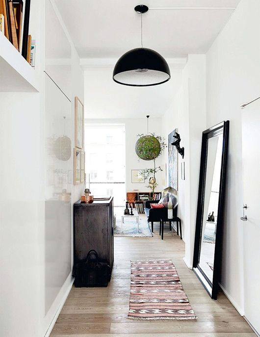 light bright hallway with modern simple black hanging lamp, mirror, woven textile runner