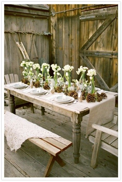 Natural table centerpieces with white flowers in clear vessels surrounded by pinecones.