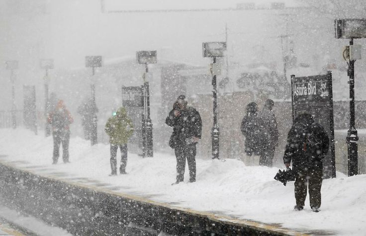 Commuters wait on the Metropolitan Transportation Authority platform for a train in heavy snow in Queens