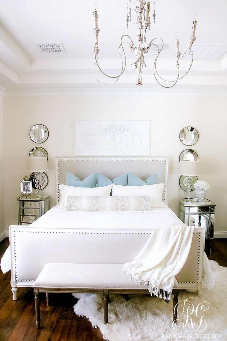 White master bedroom with blue velvet pillows and antelope bolster pillow. Headboard with nailhead trim, antique chandelier from New Orleans. Soothing Summer Home Tour 2017 - Neutral Transitional Home Decor
