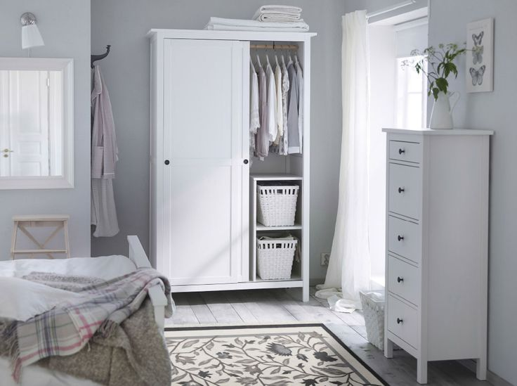 A traditional white bedroom with HEMNES wardrobe and chest of drawers in white.