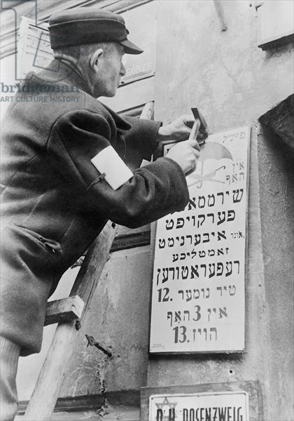 A worker in the Warsaw Ghetto exchanging a German or Polish language company nameplate for one translated into Hebrew, Warsaw, May 1941