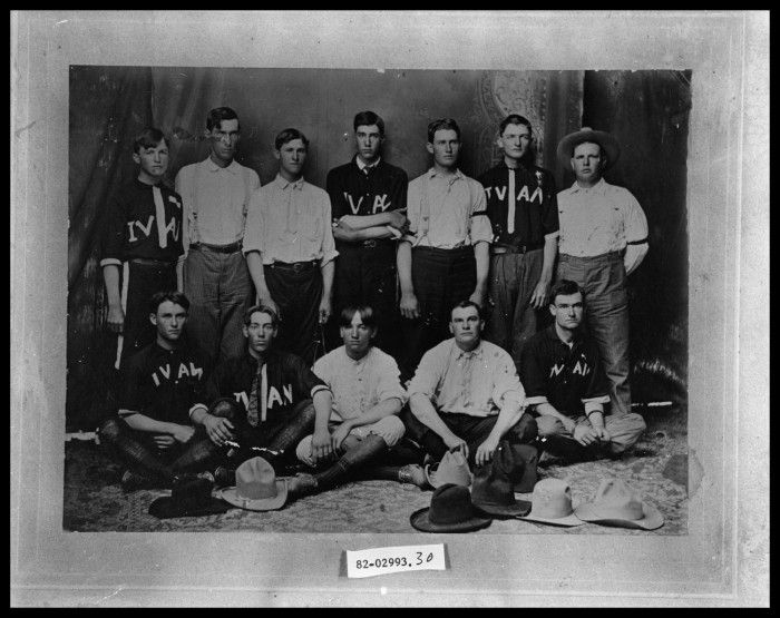 Copy negative the Ivan, Texas baseball team. The group includes Blanton Norton, Len Martin, Sterling Weatherford, Drew Johnson, Slate Walker, Walter Watkins, Pete Delong, Elmer Milam, Walter Milam, Wesley Weatherford and Jim Norton. Six of the men are wearing baseball uniforms and six are wearing button-up shirts, including one man wearing a hat. Eight cowboy hats are on the floor in front of the group.
