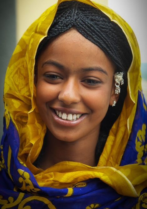 Ancient Egyptian Tripartite hairstyle on this Eritrean woman. The braids diadem contour her forehead and runs along the middle top of her head down the back, as it separates the scalp in two.