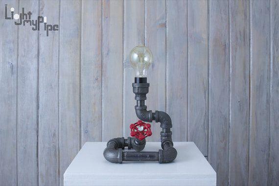 Cette lampe de table style industriel enroulée comme un serpent, est construite avec tuyau de fer noir. Le bouton du robinet agit comme interrupteur marche/arrêt. Vintage style twisted fil cordon électrique avec prise vintage. Faite avec tous les composants électriques listé UL.  Peut être livré avec un cordon noir ou rouge et noir ou manette rouge.  6.5 W x 6,5 « D x 7,5 » H