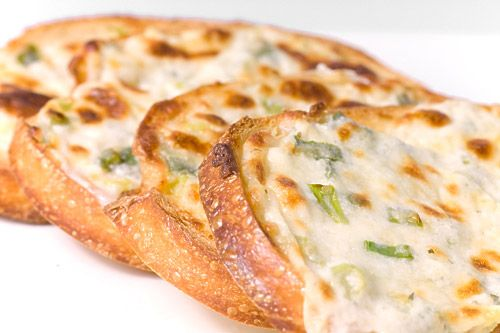 The ultimate garlic cheese bread with mozzarella, romano, garlic and herb cheese spread, green onions and mayo. Crunchy, cheesy, garlicky.