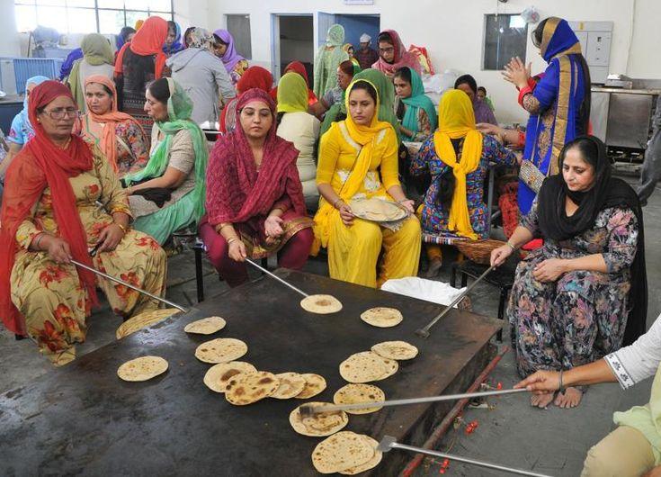 Sikh women cooking rotis on a large tawa - langar