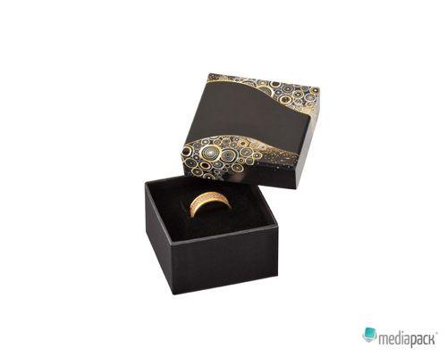 Caixa preta com decorações douradas e espuma no interior para colocação de jóias.