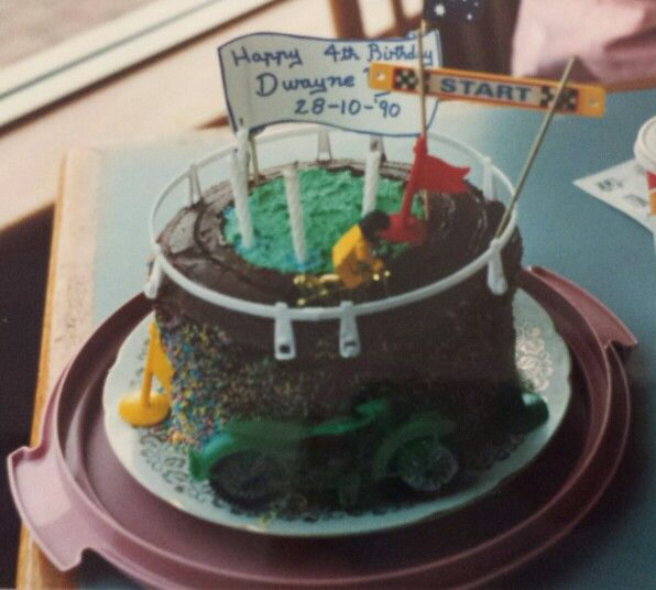 1990 Bike Track Cake. Cocolate butter icing with colored sprinkles on side and green icing centre of track. (Racing car set rails used for outer guards)