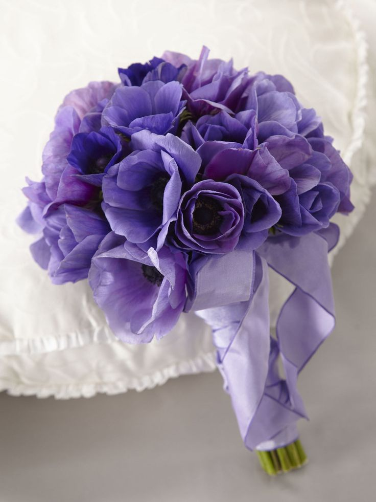 Lavender and purple anemone blooms will capture everyone's attention with their bold hues. Tied together with a lavender taffeta ribbon, this bouquet is the perfect accompaniment to your trip down the aisle.
