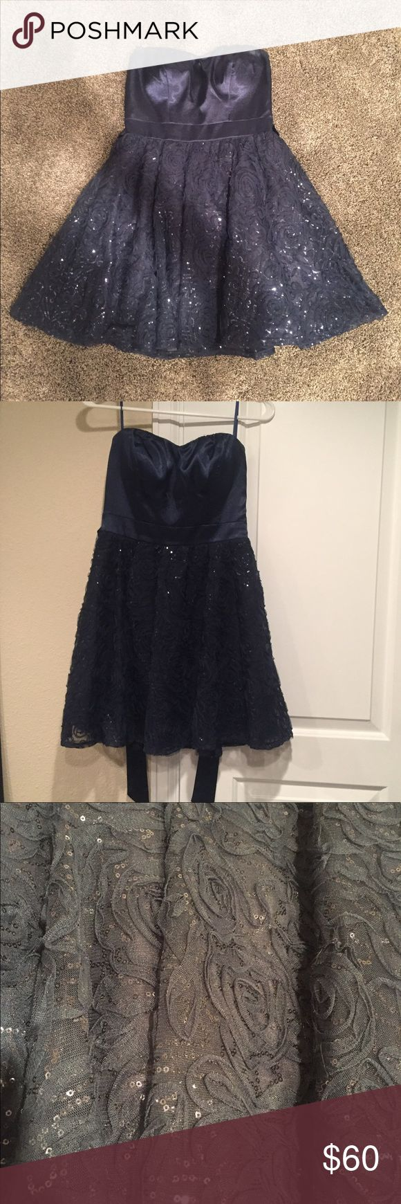 Homecoming/Prom Dress Navy blue strapless dress. Top is a silky sort of fabric and bottom has rose details and sparkles, with a silky tie around the waist. Says size seven but fits more like a 4. Only worn once. Dresses Prom