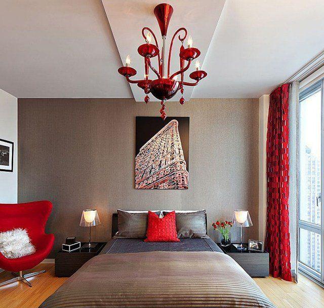chambre à coucher adulte avec fauteuil, lustre et rideaux rouges