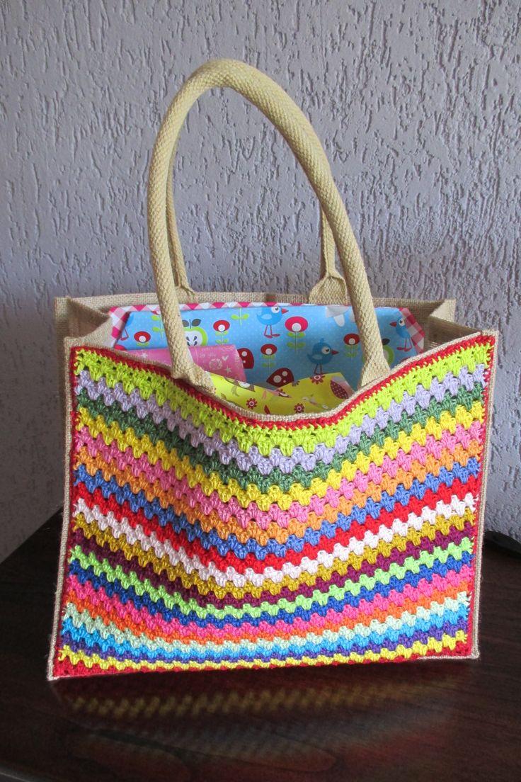 Gehaakte tas gemaakt met vrolijke kleurtjes katoenen garen. Deze heeft dienst gedaan als plaatsvervangende kraammand met kraamcadeautjes bij de geboorte van mijn kleinzoon.