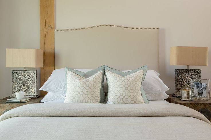 This bespoke headboard by Kirkby Design elegantly sets a neutral tone for this country-style bedroom creating an ambience of tranquillity and comfort.