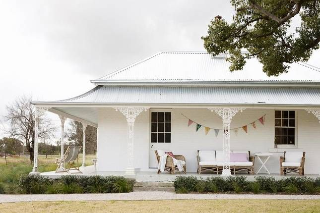 Such a pretty wooden country house with wrap around porch.
