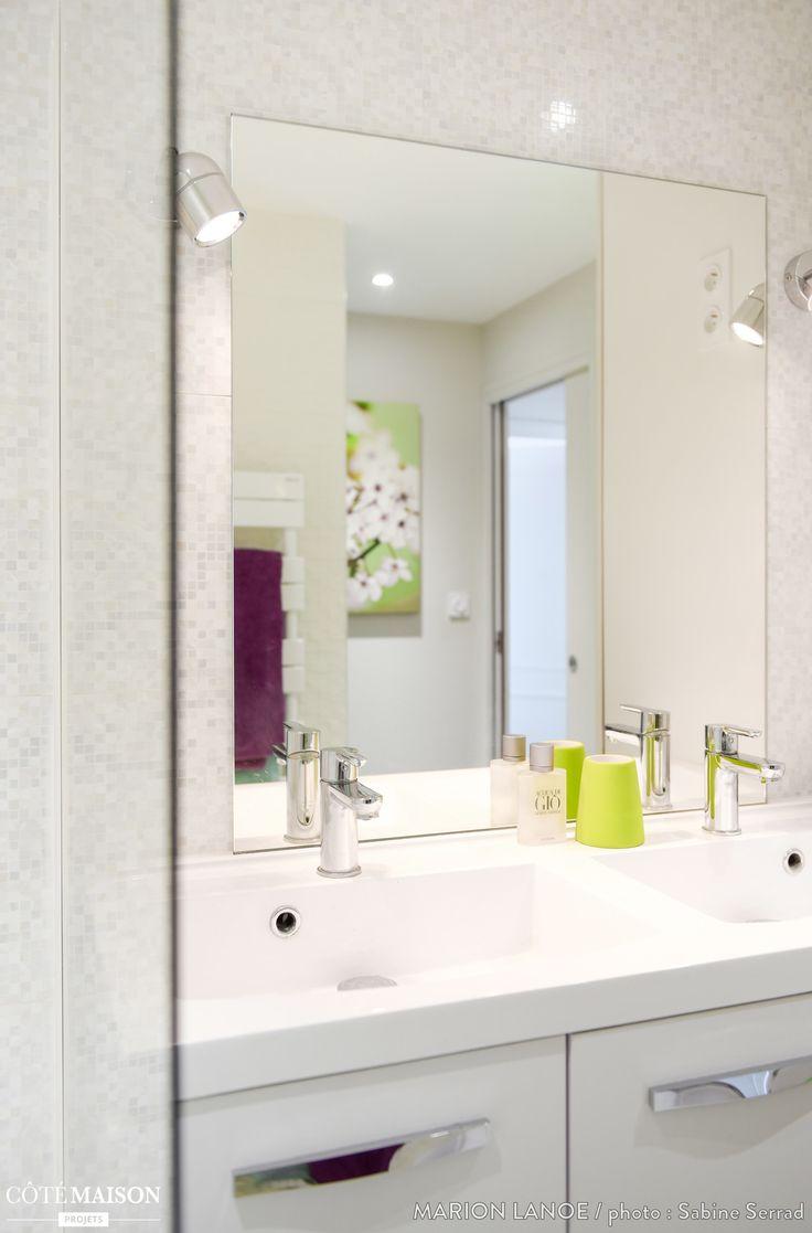 Une salle de bains blanche, lumineuse et moderne, avec un grand miroir qui reflètent l'espace.