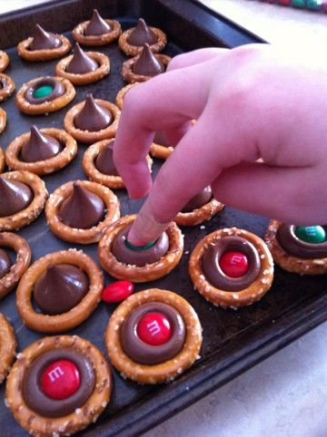 Christmas pretzels. Pretzels, Hershey's Kiss/Hug, M&M's. Pretzel + Kiss = 275° for 2-4min, top w/M&M.