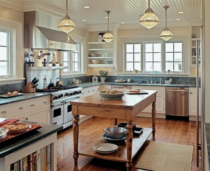 Nautical kitchen features a beadboard ceiling dotted with nautical pendants illuminating a farmhouse island facing a stainless steel refrigerator.