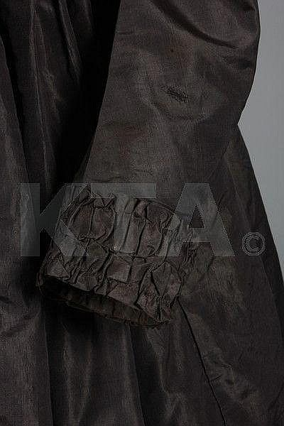 A smoke grey-brown silk taffeta dress, early 19th century but altered in the late 1830s-early 1840s, front closing by hooks and eyes, inner tan cotton breast panels, long sleeves edged in ruffles, curving back seams, the skirt tightly gathered and fastened by prestuds; together with the remains of a black silk parasol c.1870; a cotton camisole; a muslin appliqué parasol cover c.1910; a gentleman's figured silk waistcoat with enamelled gilt buttons c.1845-50; and a chenille embroidered satin…
