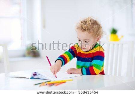 Cute little boy doing homework, reading a book, coloring pages, writing and painting. Children paint. Kids draw. Preschooler with books at home. Preschoolers learn to write and read. Creative toddler.