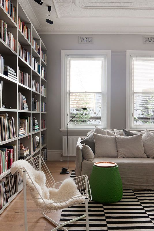 Całą ścianę tego salonu zabudowano regałem-biblioteką. Mebla celowo nie pociągnięto do samego sufitu, żeby nie zasłaniać zdobiących go oryginalnych sztukaterii. Reszta wyposażenia tego pokoju to mieszanka różnych stylów - kanapa jest klasyczna, dywan skandynawski, a ażurowy fotel i lampa podłogowa to industrialne akcenty.