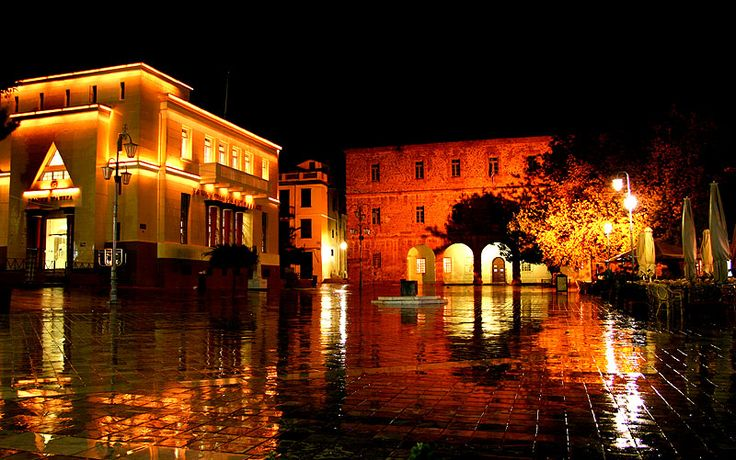Syntagma Square at the heart of the old town of Nafplio. On the left: branch of the National Bank of Greece. Far end: Archeological Museum of Nafplio.