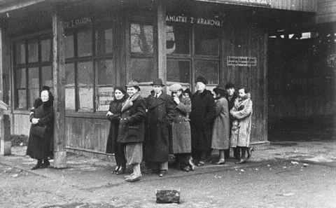 Krakow Ghetto (480Wx297H) - Jews wait in line in Krakow Ghetto. The sign in Polish reads,