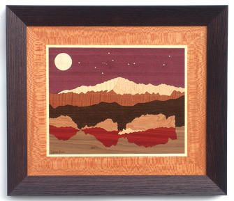"Pikes Peak above Garden of the God's rock formation wood inlay/marquetry. Named for explorer Zebulon Pike, this majestic mountain graces the Colorado Springs skyline. The woods used in this scene are: Purpleheart, Brass, Sycamore, Sycamore, Curly Maple, Makore, Wenge, Cherry, Bloodwood, Figured Walnut. Stars are brass. Size: 18"" x 21"". Available in other sizes, borders and frames - see website."