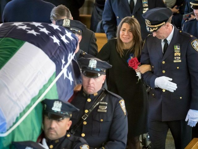 Lisa Tuozzolo, wife of the late Sgt. Paul Tuozzolo is escorted by a high  ranking New York Police Department officer, at the conclusion of Tuozzolo's Mass of Christian Burial at St. Rose of Lima Catholic Church in Massapequa, N.Y., Thursday Nov. 10, 2016.The 19-year veteran officer was killed Nov. 4, during a gun fight in the Bronx borough of New York. (J. Conrad Williams Jr./Newsday via AP, Pool) Report: Trump Personally Calls Slain NYPD Officer's Widow Offering Condolences