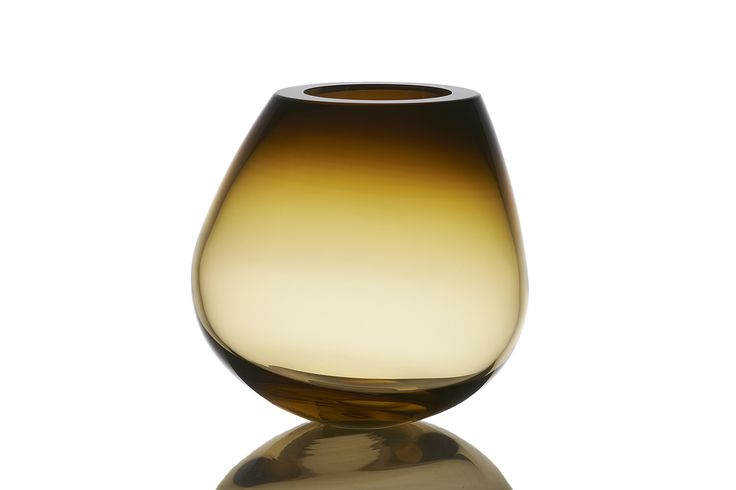 The COGNAC vase/sculpture, designed by PIECE OF DENMARK, is hand blown at a glass studio in Scandinavia, ground and polished in the traditional Scandinavian style.  The inspiration for the COGNAC is taken from the classic cognac glass. The very simple mode of expression gives the vase a sharp, sculptural character, and due to its small tilt the vase continually changes its expression.  It takes considerable professional competency and skill to hand blow the vase and control the…