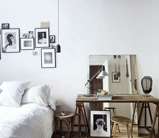wood desk in white bedroom with black and white photos. / sfgirlbybay