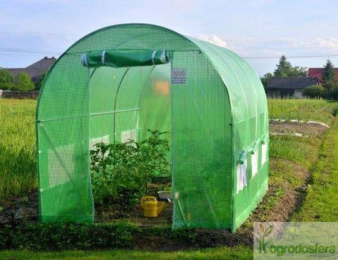 Tunel z zieloną folią zabezpieczającą rośliny przed podmuchami wiatru i szkodnikami.