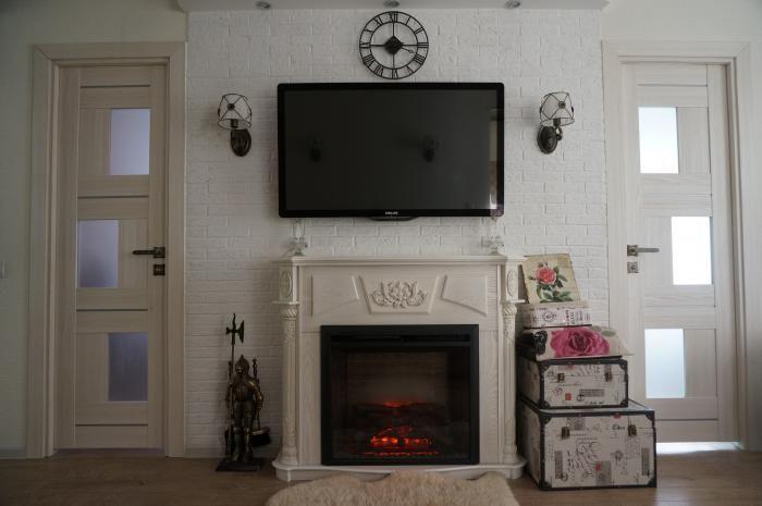 Кухня-гостиная, интерьер с камином, телевизор над камином