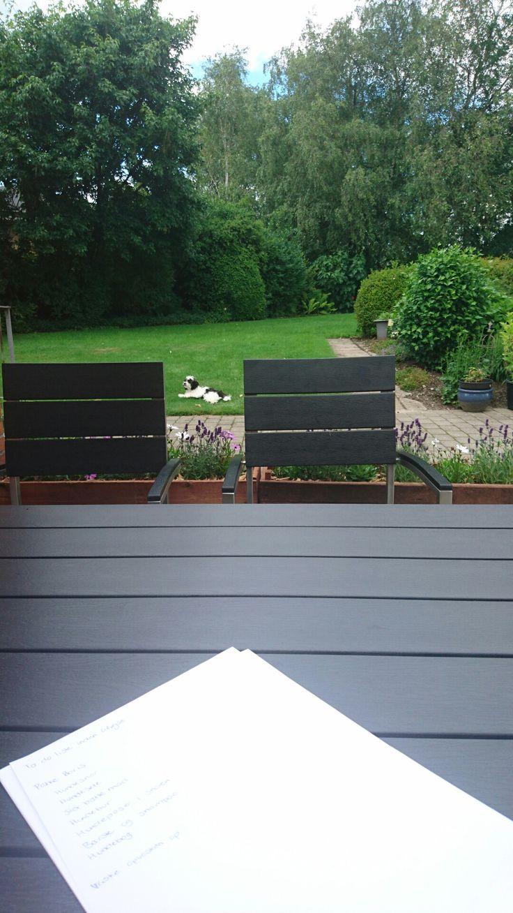 Den lille terrasse tager så småt form. 3 hjemmelavede blomsterkasser tilplantet med lavendel og margueriter, med groft flis som bunddække danner sammen med en krukke med en flot lyserød hortensia rammerne for terrassen, hvorpå der er står et sort havebord med tilhørende fire stole.