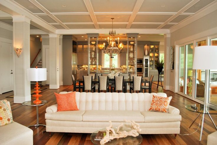 Living room features white couch, orange accents, glass and metal tables, and full dining area in background.