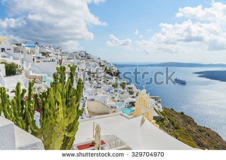 Picturesque cactuses and romantic greek houses above the bay, with view on caldera and vulcan .Santorini (Thira) island.Cyclades.Greece.Europe.