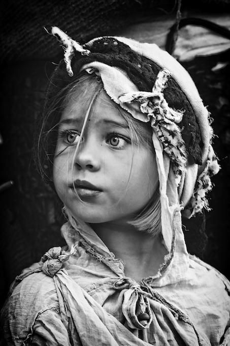 A young girl  from a struggling life who still has hopes and aspirations.   :                           I really like the contrast between black and white because it brings attention to her eyes. Although it is a photograph, it captures her cultural heritage as well through her head dress and clothing which depicts her story.