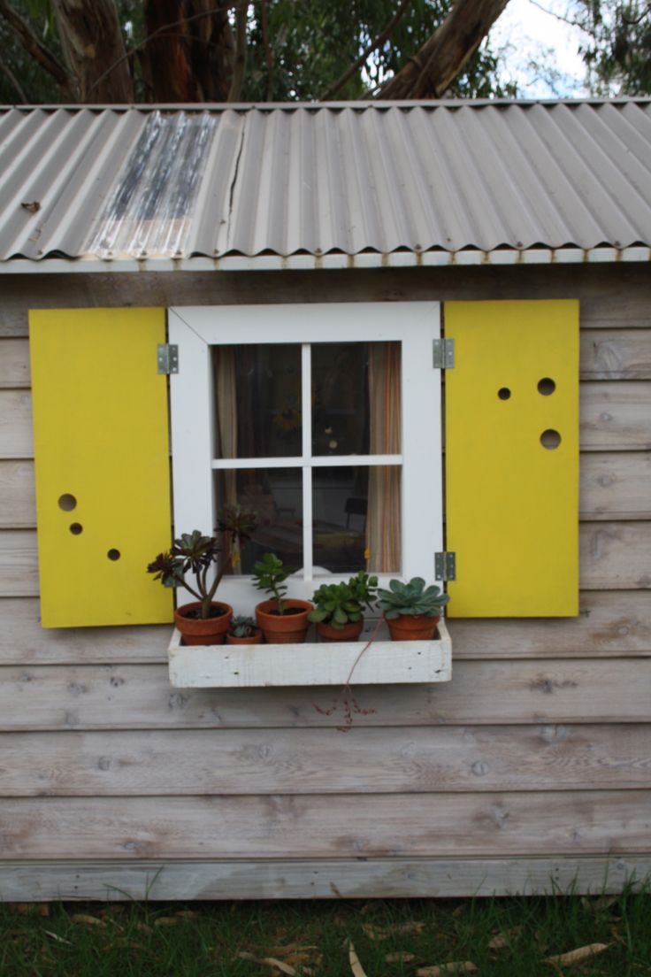 Cubby House with white window frame & bright shutters - simply