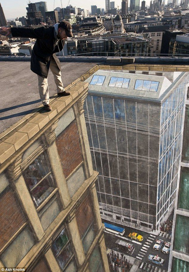 Inches from death... or really? Pavement artist stands on the edge of his drawing of a New York scene - in London