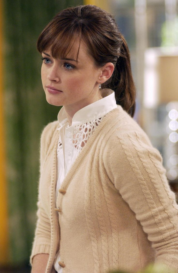 I love the lace bib on the shirt and the beige cardigan with the delicate hints of cable knit.